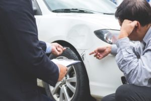 insurance agent taking notes about car accident