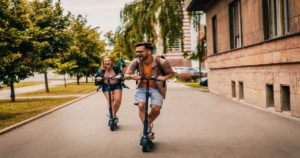 a man and woman riding scooter